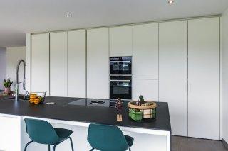 Greeploze keuken in strak wit met BORA kooksysteem.