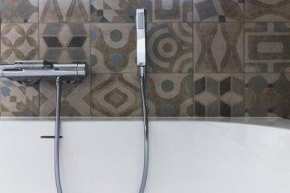Voor deze badkamer in Geetbets koos de klant voor een decortegel. Deze tegels zijn een echte trend dit jaar. Op de foto is een detail te zien van het bad, de kraan en de gekozen tegels..